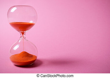Hourglass with orange sand on pink background.