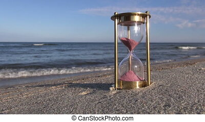 Hourglass sandglass with pink sand on the beach by the sea on sunny evening