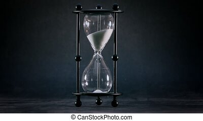 Hourglass with white sand against dark background closeup