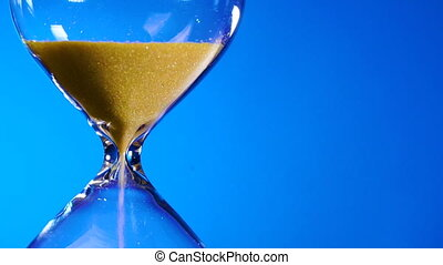 Hourglass yellow sand in a transparent flask is strewed on a blue background and time is running out.