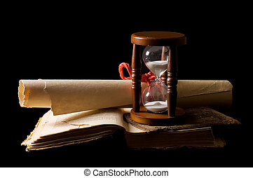 Hourglasses and book On black a background