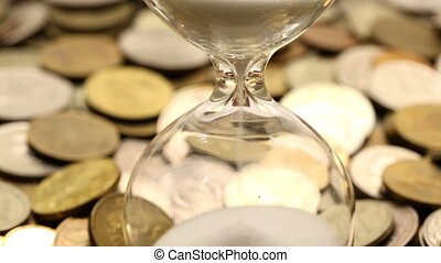 Hourglasses and coins, time is money concept