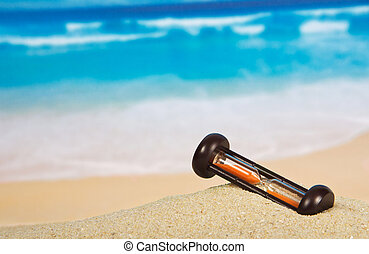Hourglasses on a sandy beach