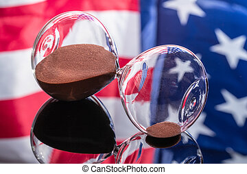 Hourglasses on mirror background with American flag reflected in it. Independence Day concept