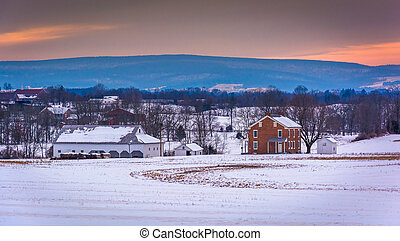 House and barn in a snow-covered farm field in Gettysburg,...