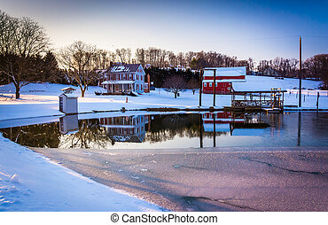 House and barn reflecting in a semi-frozen pond in rural York County, Pennsylvania.