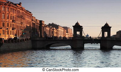 House and Bridge Lomonosov at canal illuminated by setting sun in center St. Petersburg