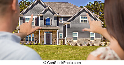 House and Military Couple Framing Hands in Front