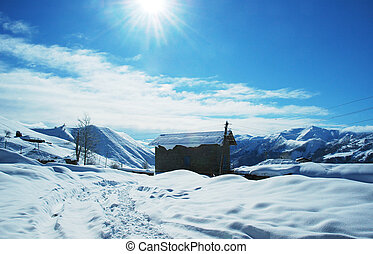 House and mountains in the bright winter day