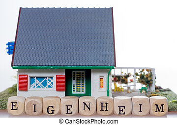 Home Ownership - House and wooden dice with the german word...