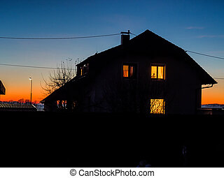 house at night with light in windows - house with lighted...