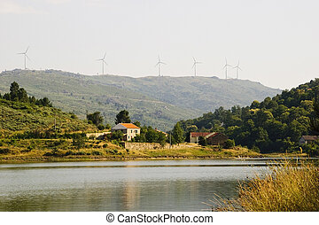 House at the lake with wind turbines