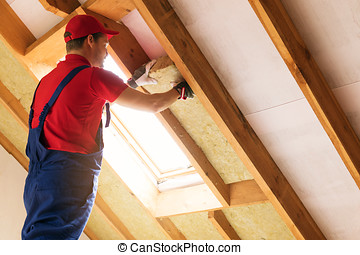 house attic insulation - construction worker installing rock...