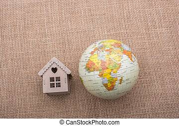 House beside a globe placed on canvas background