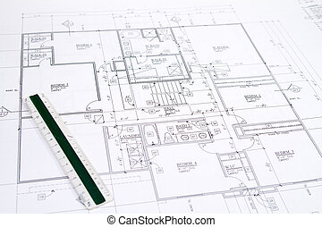 Residential home blueprints with a hand-made house model.