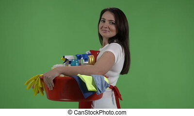 House cleaning service. Woman holds washbowl with washing fluids and rags against green screen.
