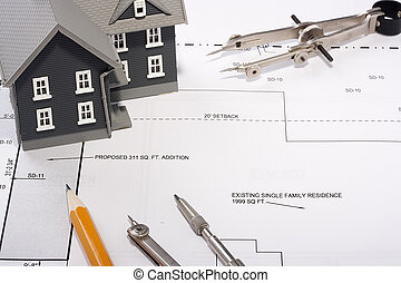 House Construction - House model and drafting tools on a ...