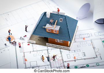house construction project concept. building scale model and workers on blueprint