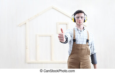 house construction renovation concept handyman carpenter worker man like hand thumb up with the model of a wooden house on background
