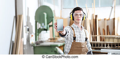 house construction renovation concept handyman carpenter worker man show the mobile phone isolated with the model of a wooden house on background