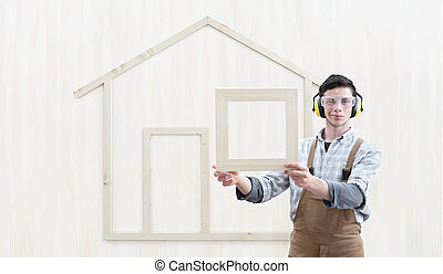house construction renovation concept handyman carpenter worker man show the model of a wooden house isolated on wood background
