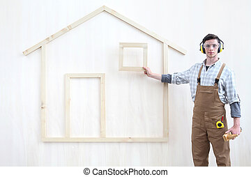 house construction renovation concept handyman carpenter worker man show the model of a wooden house