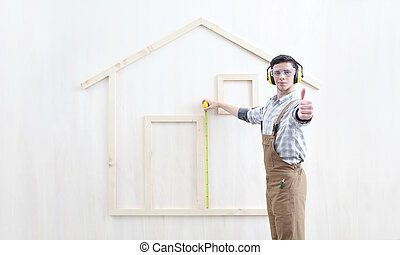 house construction renovation concept handyman carpenter worker man with meter measure and show the model of a wooden house, like hand thumb up for custom solutions
