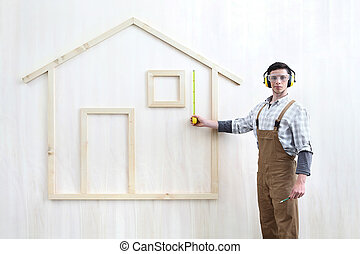 house construction renovation concept handyman carpenter worker man with meter measure and show the model of a wooden house, custom solutions