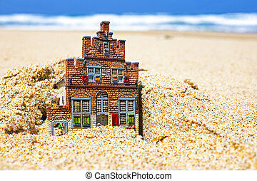 House disappearing in the sand. Concept for real estate in...