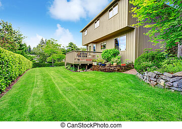 House exterior. Backyard view - Wood siding house with...