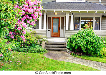 House exterior. View of entrance column porch with stairs and walkway.