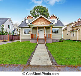 Small house with wooden column porch. View from walkway