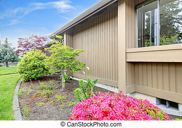 House exterior. View of wall with flower bed