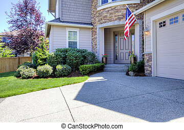 House exterior with driveway and American flag.