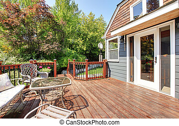 House exterior with large open deck with outdoor furniture....