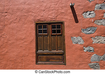 house facade and window with closed wooden shutters -