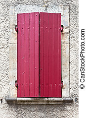 House facade with red shutters in France