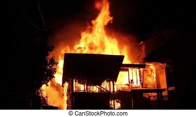 House fire fully involved in flames and spreading to adjacent houses