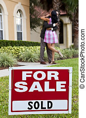 House For Sale and Sold sign with African American couple celebrating the purchase of a house out of focus behind the sign.