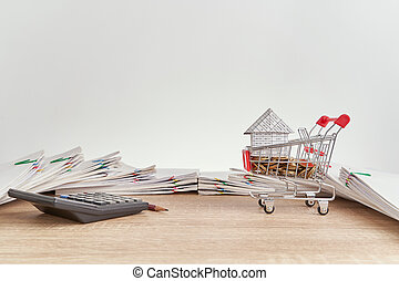 House gold coins in shopping cart and calculator with pencil