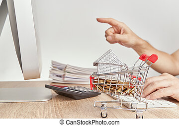 House gold coins in shopping cart have blur pointing finger