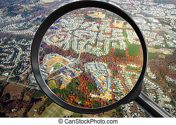 Neighborhood from the air with magnifying glass - real estate concept