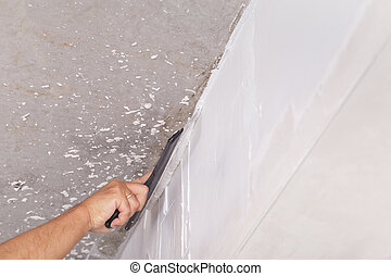 house improvement by worker puts finishing layer of stucco on the wall using a plastering trowel