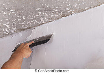 house improvement worker puts finishing layer of stucco on wall