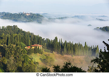 House in green and foggy Tuscany hillside