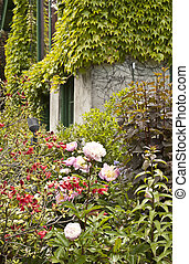House in the Garden - Flowers and vines surround a home in a...