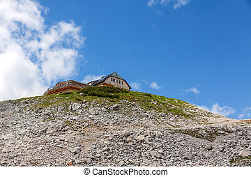 House in the mountains at a slope with rocks and scree