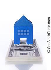 House investment - blue toy house over a lot of dollar bills...