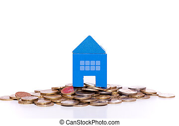 House investment - blue toy house over a lot of golden coins...