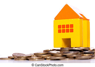 House investment - yellow toy house over a lot of golden...